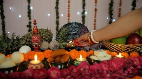 Indian female's hand lighting up a Diya in front of Hindu idol Goddess Durga