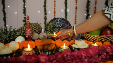 Bengali woman's hand placing a burning oil lamp in front of Ma Durga's idol