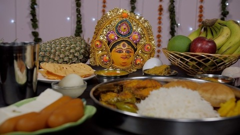 Zoom in shot of a Bengali Prasad/Bhog placed in front of Goddess Durga's idol