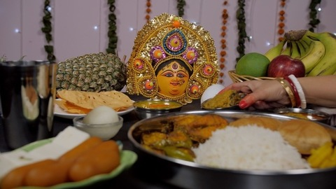 Bengali married woman's hand keeping fish curry (Macher Jhal) with Bhog items