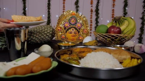 Religious Bengali female keeping a plate of Papad before Devi Durga as Bhog/Prasad/Offering
