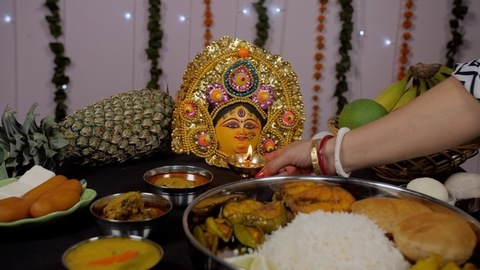 Bengali married woman's hand keeping a Diya in front of Ma Durga during Puja