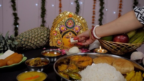 Married Bengali woman offering Sandesh to Ma Durga during prayers