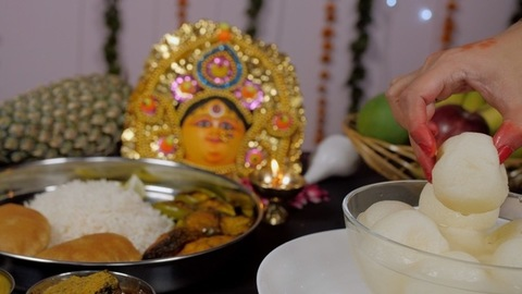 Bengali woman's beautiful hand taking a Rosogolla from a bowl of Bhog/Prasad