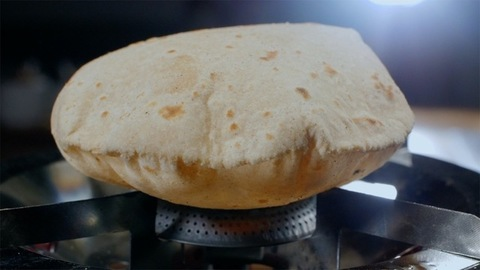 Closeup shot - Making of fresh wheat Indian chapatis on a gas stove at home