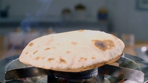 Indian cook making fresh chapatis on a gas stove using a tong - cooking concept