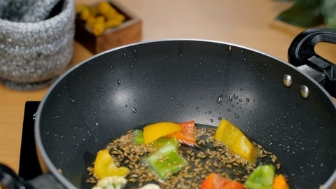 Closeup shot of adding colorful vegetables in a frying pan - cooking concept