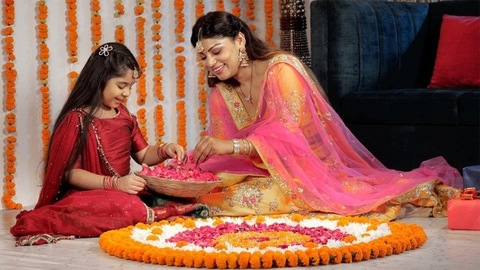 A happy mother and daughter decorating a traditional Rangoli with rose petals