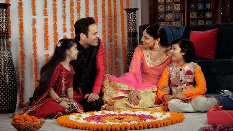 Attractive parents happily enjoying Diwali holidays with their children at home