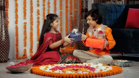 Happy brother and sister in ethnic attire exchanging gifts during a Hindu festival