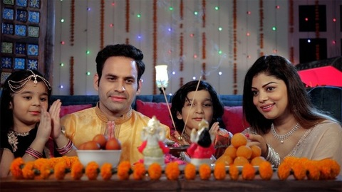 A married couple happily doing an Aarti / Puja at home with their children