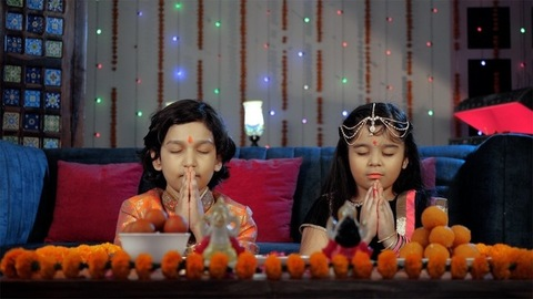 Happy siblings in an ethnic dress doing a religious Diwali Puja together