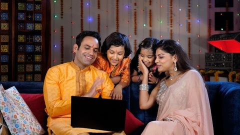Cheerful parents and their kids waving their hands while talking on a video call - a celebration time
