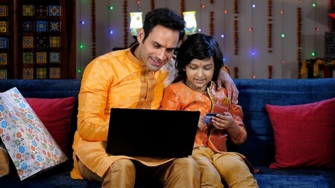Sweet little kid in traditional wear helping his father for online shopping