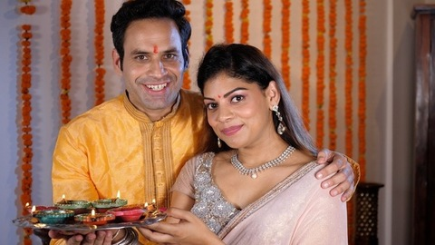A married couple celebrating the festival of Diwali with a plate of well lit Diyas