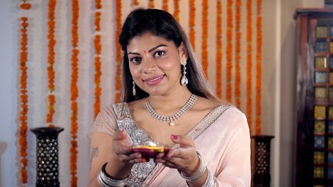 An attractive female wearing colorful jewelry holding a well-lit Diya for Diwali
