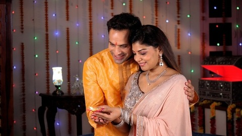Indian husband-wife holding a well-lit clay Diya on the occasion of Diwali - Love and Bonding