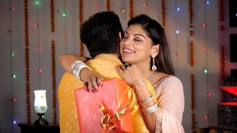 Beautiful lady in a pretty Saree hugging her partner while holding a gift box - a celebration time