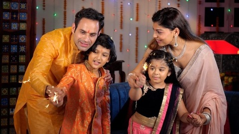 Small nuclear family burning firecrackers / Phuljhadis with their children - festive season