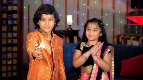 Kids celebrating Diwali by burning firecrackers / phuljhari