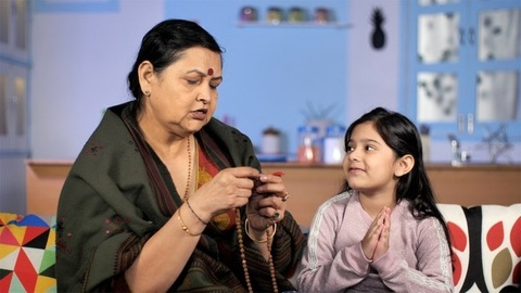 A middle-aged woman and her grandchild praying while sitting in their home