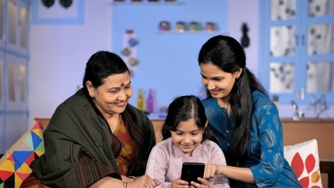 Cheerful three generations of women using a smartphone together at home