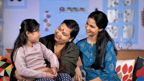 Sweet little Indian girl getting love and affection from her grandmother and mother
