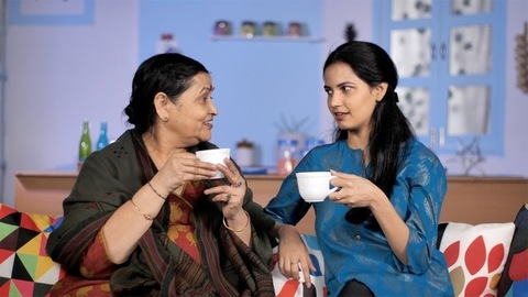 An elderly lady enjoying a cup of tea / coffee sitting with her daughter