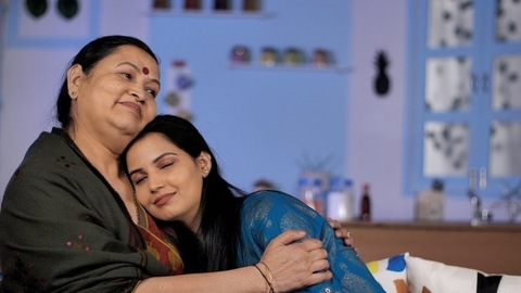 An aged mom hugging her grown-up daughter at home - happy moment