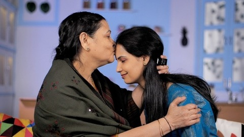A middle-aged Indian mother kissing her daughter with love - happy family