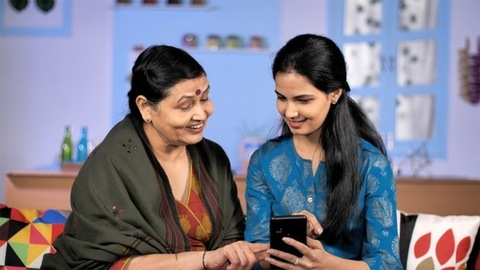 Happy mature Indian lady and her young grownup daughter spending time on mobile