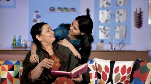 Loving Indian woman hugging her old mother sitting on a couch - family bonding