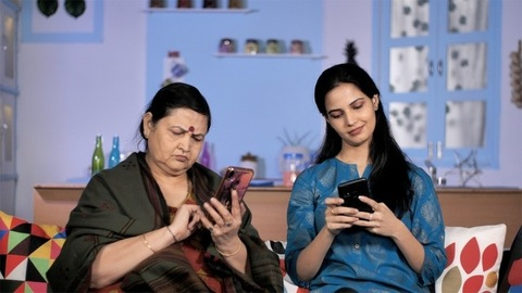 Urban Indian women busy on their smartphones sitting on a couch at their home