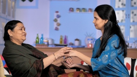 Lovely adult daughter giving the medicines to her sick elderly mother at home