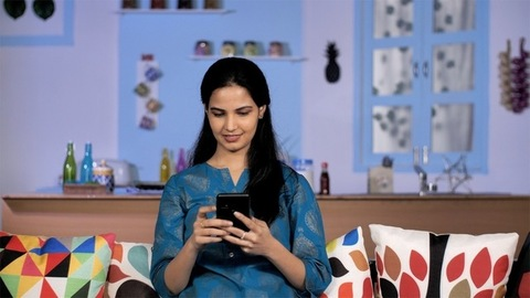 Pretty young Indian woman browsing the internet on mobile - modern technology