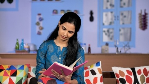 A lovely Indian woman reading an interesting book indoors - stay home concept