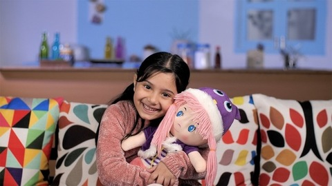 Cute little school-age girl cuddling her favorite soft doll sitting at her home - Indian kid