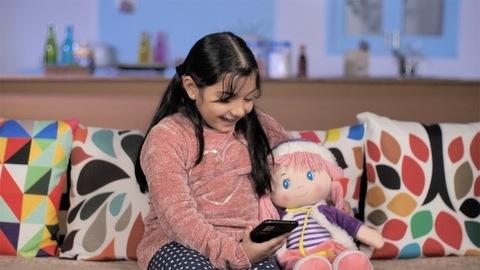 Lovely little girl using mobile sitting at her home - modern technology