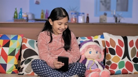 Small urban child sitting with a doll enjoying funny videos on a smartphone