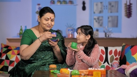 Joyous little girl and her grandmother playing with toy tableware at home