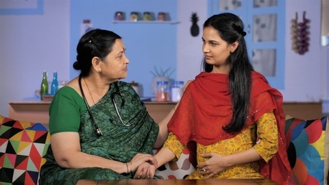 Mature Indian doctor talking to a pregnant woman enquiring about her health