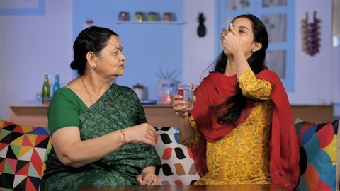 Caring elderly Indian mother giving pills to her pregnant daughter - love and support