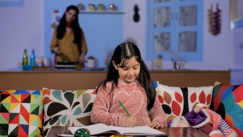 School going girl child studying while her mother is cooking in the modern kitchen