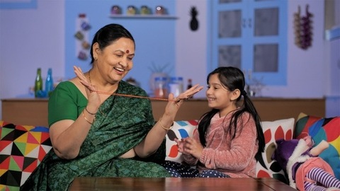 Cheerful grandma and her school-age granddaughter playing cats cradle at home