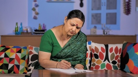 Portrait of a mature Indian lady filing up a form sitting on a couch indoors