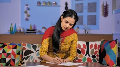 Young Indian homemaker puts a signature on an official paper - Insurance documentation
