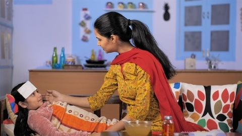 Young and beautiful Indian mother taking care of her sick girl child - Love and care in family