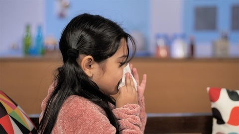 Portrait of a small sick child sneezing and blowing nose - viral infection / cold / coronavirus