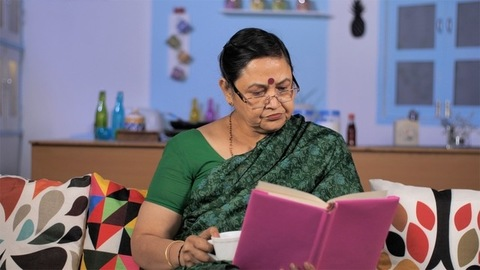Old Indian lady with spectacles reading a book indoors - book reading hobby