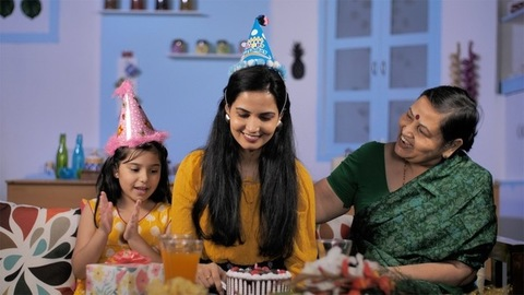 A young woman with a party cap cutting her birthday cake sitting with family
